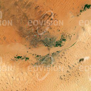 """Das Satellitenbild """"CHINGUETTI - Mauretanien"""" ist dem Bildband """"CITIES - Brennpunkte der Menschheit"""" entnommen. Bildbeschreibung: Die mauretanische Stadt liegt in einer schon vor Jahrtausenden besiedelten Region im Westen der Sahara. Das heutige Chinguetti wurde im 13. Jahrhundert auf einer älteren Siedlung am Schnittpunkt von Handelsrouten durch die Sahara gegründet und spielte lange eine wichtige Rolle als befestigter Handelsstützpunkt. Durch Änderungen im globalen Handel sank in den beiden letzten Jahrhunderten die Bedeutung der Karawanenrouten. Die Einwohnerzahl ging zurück und die Wüste breitete sich in die Stadt aus."""