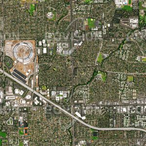 """Das Satellitenbild """"CUPERTINO - APPLE - USA"""" ist dem Bildband """"CITIES - Brennpunkte der Menschheit"""" entnommen. Bildbeschreibung: Das kalifornische Silicon Valley zeigt beispielhaft, wie sich Entwicklungen in Städten wechselseitig verstärken. Hier waren es die Universitäten, die zur Ansiedlung von High-Tech-Firmen im Bereich der Informationstechnologien führten. Diese wiederum schufen Arbeitsplätze für hochqualifizierte Universitätsabsolventen. Ein Beispiel eines in diesem Umfeld gewachsenen Unternehmens ist Apple, dessen in Bau befindlicher neuer, kreisförmiger Campus für 13.000 Angestellte in der Aufnahme zu sehen ist."""