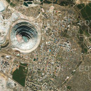"""Das Satellitenbild """"MIRNY - Russland"""" ist dem Bildband """"CITIES - Brennpunkte der Menschheit"""" entnommen. Bildbeschreibung: Mirny wurde im Jahr 1955 nach dem Fund der ersten sibirischen Diamantvorkommen gegründet, um diese auszubeuten. Die Bergbaustadt im Permafrostgebiet des russischen Jakutien ist unmittelbar um die Diamantmine Mir angeordnet, mit 525 Meter Tiefe und 1,2 Kilometern Durchmesser eine der weltweit größten Minen im Tagebau. Nachdem die Diamantförderung stark zurückgegangen war, wurde die Mine ab dem Jahr 2001 schrittweise geschlossen."""