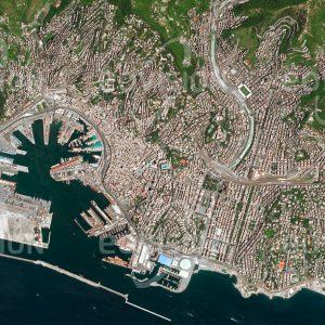 """Das Satellitenbild """"GENUA - Italien"""" ist dem Bildband """"CITIES - Brennpunkte der Menschheit"""" entnommen. Bildbeschreibung: Für die italienische Stadt spielte von Anfang an der große natürliche Hafen eine wichtige Rolle. Er ermöglichte Genua im Mittelalter die Entwicklung zu einer der bedeutendsten Handelsstädte Europas, bevor Venedig die Vorherrschaft errang. Auch heute ist der Containerhafen Genuas einer der größten des Mittelmeers und versorgt ganz Nordostitalien. Die räumliche Entfaltung der Stadt ist durch die Lage zwischen Mittelmeer und den Ausläufern des Appenins eingeschränkt."""