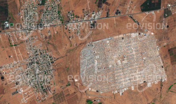 """Das Satellitenbild """"AZ-ZAATARI - Jordanien"""" ist dem Bildband """"CITIES - Brennpunkte der Menschheit"""" entnommen. Bildbeschreibung: Kriegerische Konflikte sind der häufigste Grund, dass Menschen ihre Heimat verlassen, und so wie Konflikte sind auch Flüchtlingslager kein neues Phänomen. Az-Zaatari im Norden Jordaniens gehört mit fast 80.000 Bewohnern zu den größten Flüchtlingslagern der Welt. Es entstand ab 2012 als Folge des syrischen Bürgerkriegs, durch den bis 2015 fast 12 Millionen Menschen vertrieben wurden. Unter der Leitung des UNHCR (Flüchtlingswerk der Vereinten Nationen) ist eine große Zahl internationaler und nationaler jordanischer Organisationen mit der Verwaltung des Lagers beschäftigt, das sich immer mehr zu einer eigenen Stadt entwickelt."""