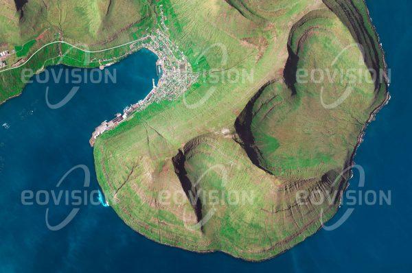 """Das Satellitenbild """"FUGLAFJØRDUR FÄRÖER - Dänemark"""" ist dem Bildband """"EUROPA - Kontinent der Vielfalt"""" entnommen. Bildbeschreibung: Inmitten des Europäischen Nordmeeres liegen die zu Dänemark gehörigen, aber weitgehend autonomen Färöer, die ab dem neunten Jahrhundert von Wikingern besiedelt wurden. Die Wirtschaft der Inseln beruht zu einem großen Teil auf Fischerei und Fischzucht. Umstritten ist der Walfang, dem auf den Färöern jährlich mehrere Hundert Wale zum Opfer fallen."""