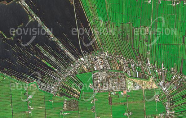"""Das Satellitenbild """"DE RONDE VENEN - Niederlande"""" ist dem Bildband """"EUROPA - Kontinent der Vielfalt"""" entnommen. Bildbeschreibung: Die niederländische Gemeinde De Ronde Venen liegt bis zu sechs Meter unterhalb des Meeresspiegels und ist daher auf den Schutz durch Deiche und Pumpen angewiesen. Das Moorgebiet wird seit etwa 1000 Jahren kultiviert. Die radial von den Siedlungen im Zentrum nach außen führenden Entwässerungsgräben sind in der Aufnahme gut zu erkennen. Durch Torfgewinnung entstand im Laufe der Jahrhunderte der im Norden sichtbare See. Heute werden die Wasserflächen als Angelrevier und für Wassersport genutzt."""