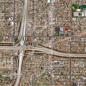 """Das Satellitenbild """"LOS ANGELES - USA"""" ist dem Bildband """"HUMAN FOOTPRINT - Satellitenbilder dokumentieren menschliches Handeln"""" entnommen. Bildbeschreibung: Infolge der Nähe von Los Angeles zur San-Andreas-Spalte treten hier immer wieder schwere Erdbeben auf, wie zuletzt 1994. Daher ist die Anzahl von Wolkenkratzern sehr gering, mit der Folge eines großen Flächenbedarfs für Wohnbau und auch für die Verkehrsinfrastruktur. Trotz breiter Straßen mit bis zu 15 Spuren, die in Kreuzungen in mehreren Stockwerken übereinander geführt werden, sind Staus in Los Angeles an der Tagesordnung."""