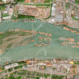 """Das Satellitenbild """"FRASER MILLS - Kanada"""" ist dem Bildband """"HUMAN FOOTPRINT - Satellitenbilder dokumentieren menschliches Handeln"""" entnommen. Bildbeschreibung: Im Einzugsgebiet des Fraser gefällte Baumstämme treiben als Flöße gebündelt den Fluss hinab, bis sie wie hier in Fraser Mills gesammelt und weiterverarbeitet werden."""
