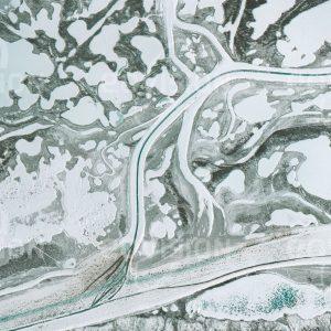 """Das Satellitenbild """"INUVIK - Kanada"""" ist dem Bildband """"HUMAN FOOTPRINT - Satellitenbilder dokumentieren menschliches Handeln"""" entnommen. Bildbeschreibung: Im Winter werden die eisbedeckten arktischen Flüsse als Autobahnen genutzt, deren Fahrbahnen im Frühling durch dunkles, blankes Eis erkennbar sind."""