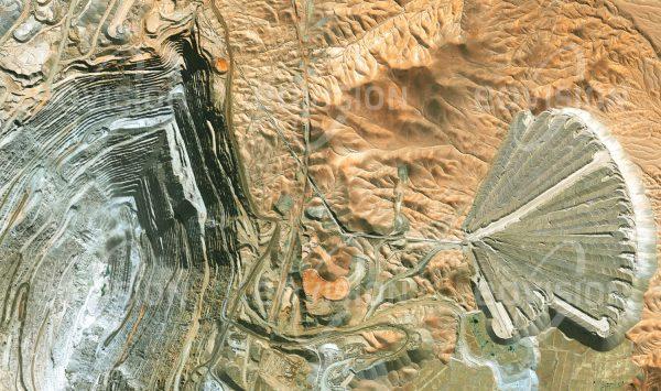 """Das Satellitenbild """"CALAMA - Chile"""" ist dem Bildband """"HUMAN FOOTPRINT - Satellitenbilder dokumentieren menschliches Handeln"""" entnommen. Bildbeschreibung: In der chilenischen Wüste Atacama befindet sich die nach der Escondida-Mine weltweit produktivste Kupfermine Chuquicamata. Die enormen Abraummengen der mit 4,3 Kilometern Länge, 3 Kilometern Breite und mehr als 900 Metern Tiefe weltgrößten Kupfermine werden unweit der Grube fächerförmig wieder angehäuft. Bisher wurden in Chuquicamata etwa 30 Millionen Tonnen Kupfer gefördert."""