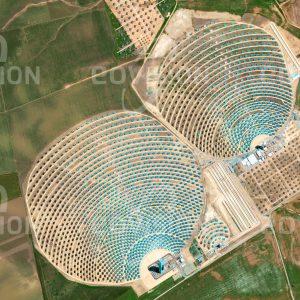 """Das Satellitenbild """"SEVILLA - Spanien"""" ist dem Bildband """"HUMAN FOOTPRINT - Satellitenbilder dokumentieren menschliches Handeln"""" entnommen. Bildbeschreibung: Die sonnigen, trockenen Gebiete Südspaniens eignen sich hervorragend für die Nutzung der Sonnenenergie wie hier in den Solarturmkraftwerken bei Sevilla. Hunderte der Sonne nachgeführte Spiegel reflektieren die Sonneneinstrahlung auf die Spitze zweier Türme, wo die entstehende Temperatur von 1.000°C  zur Erzeugung elektrischer Energie mit einer Leistung von bis zu 11 bzw. 20 Megawatt genutzt wird."""