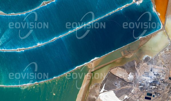 """Das Satellitenbild """"SAFI - Jordanien"""" ist dem Bildband """"HUMAN FOOTPRINT - Satellitenbilder dokumentieren menschliches Handeln"""" entnommen. Bildbeschreibung: Aus dem Wasser des Toten Meeres wird in großem Umfang mit Hilfe von ausgedehnten Verdunstungsbecken Salz gewonnen und direkt am Ufer industriell weiterverarbeitet."""