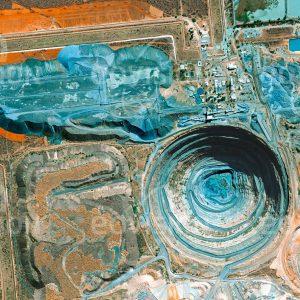 """Das Satellitenbild """"DETOIE - Botsuana"""" ist dem Bildband """"HUMAN FOOTPRINT - Satellitenbilder dokumentieren menschliches Handeln"""" entnommen. Bildbeschreibung: Botswana gehört zu den Ländern mit den bedeutendsten Diamantenvorkommen. Hier liegt auch die Orapa-Mine, die in Bezug auf die Fläche größte Diamantenmine der Welt. Entlang einem alten Vulkanschlot reicht sie mehr als 200 Meter in die Tiefe. Mehrfache Sicherungszäune umgeben das Gelände der Mine mit der Abbaustätte. Für die Förderung von etwa 2 Tonnen Diamanten werden hier jedes Jahr mehr als 60 Millionen Tonnen Gestein bewegt."""