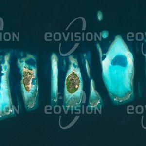 """Das Satellitenbild """"FELIDHOO - Malediven"""" ist dem Bildband """"HUMAN FOOTPRINT - Satellitenbilder dokumentieren menschliches Handeln"""" entnommen. Bildbeschreibung: Felidhoo ist ein Atoll der südwestlich von Indien gelegenen Malediven, die für ihre Palmenstrände und die üppige Unterwasserwelt bekannt sind. Großzügig ausgestattete und idyllisch am Wasser gelegene Tourismusanlagen stellen den wichtigsten Wirtschaftsfaktor der Inselgruppe dar. Da sich die Inseln nur wenige Meter über das Meer erheben, sind sie dem drohenden Anstieg des Meeresspiegels in besonderem Maße ausgeliefert."""