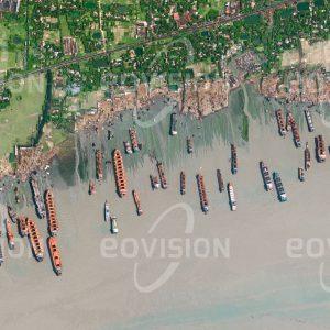 """Das Satellitenbild """"CHITTAGONG  - Bangladesch"""" ist dem Bildband """"HUMAN FOOTPRINT - Satellitenbilder dokumentieren menschliches Handeln"""" entnommen. Bildbeschreibung: Bei Chittagong liegt einer der weltweit größten Abwrackplätze für Ozeanschiffe. Ausrangierte Schiffe laufen bei Flut mit maximaler Geschwindigkeit auf den flachen Strand auf, wo sie zerlegt werden. Mehr als 25.000 Arbeiter sind hier mit dem Abwracken der Schiffe und der Weiterverarbeitung des Stahls beschäftigt. Vielfach ist dabei weder die Arbeitssicherheit noch die Einhaltung ökologischer Standards gewährleistet, sodass tödliche Unfälle an der Tagesordnung sind."""