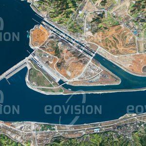 """Das Satellitenbild """"LIJIAWAN - China"""" ist dem Bildband """"HUMAN FOOTPRINT - Satellitenbilder dokumentieren menschliches Handeln"""" entnommen. Bildbeschreibung: Die Staumauer des 2008 in Vollbetrieb genommenen Drei-Schluchten-Damms staut den Jangtsekiang über 600 Kilometer zurück. Neben der Gewinnung von jährlich mehr als 80 Terawattstunden elektrischer Energie soll der Damm auch den Hochwasserschutz und die Schiffbarkeit des Flusses verbessern. Dem wirtschaftlichen Nutzen stehen gravierende ökologische und soziale Probleme für die ursprünglichen Bewohner des nun überfluteten Gebiets gegenüber."""