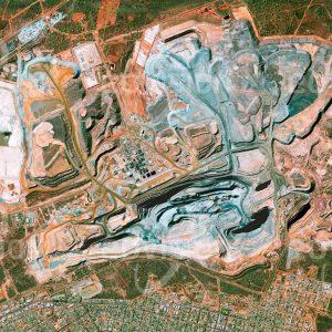 """Das Satellitenbild """"KALGOORLIE - Australien"""" ist dem Bildband """"HUMAN FOOTPRINT - Satellitenbilder dokumentieren menschliches Handeln"""" entnommen. Bildbeschreibung: Unterschiedliche Farbtöne kennzeichnen die Gesteinsschichten der Super Pit Mine nahe der Stadt Kalgoorlie im australischen Outback, wo jährlich etwa 25 Tonnen Gold gefördert werden."""