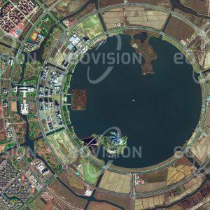 """Das Satellitenbild """"NANHUI NEW CITY - China"""" ist dem Bildband """"NEW HUMAN FOOTPRINT - Unsere Welt im Umbruch"""" entnommen. Bildbeschreibung: Bei der südlich von Shanghai am Gelben Meer gelegenen Nanhui New City zeigt sich deutlich, wie stark der Aufschwung Chinas mit einer Umgestaltung der Landschaft verbunden ist. Nach Planung durch ein deutsches Architekturbüro wurde 2003 mit dem Bau der Stadt begonnen, die ursprünglich für 500.000 Einwohner geplant war. Teil des Projekts ist der Dishui-See, der mit 5,6 Quadratkilometern der größte künstliche Süßwassersee Chinas ist. Für einen Freizeitpark, für Sportaktivitäten und für Hotels wurden jeweils eigene Inseln im See gestaltet."""