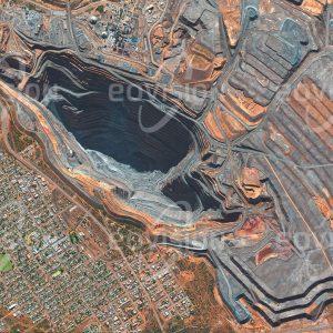 """Das Satellitenbild """"KALGOORLIE - Australien"""" ist dem Bildband """"NEW HUMAN FOOTPRINT - Unsere Welt im Umbruch"""" entnommen. Bildbeschreibung: Die im Jahr 1893 eröffnete Goldmine bei Kalgoorlie ist eine der bekanntesten Minen Australiens und war bis 2016 auch der größte Tagebau des Kontinents, weshalb sie auch den Namen Super Pit trägt. Um eine jährliche Förderleistung von etwa 28 Tonnen oder 1,5 Kubikmeter Gold zu erzielen, müssen hier jedes Jahr 15 Millionen Tonnen Gestein aus dem Felsen gesprengt und aufbereitet werden."""