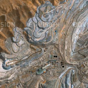 """Das Satellitenbild """"CHUQUICAMATA - Chile"""" ist dem Bildband """"NEW HUMAN FOOTPRINT - Unsere Welt im Umbruch"""" entnommen. Bildbeschreibung: Die in 2850 Metern Höhe gelegene Chuquicamata-Mine war lange Zeit die größte Tagbau-Kupfermine und mit mehr als 1000 Metern Tiefe eine der tiefsten der Welt. Bisher wurden mehr als 3 Milliarden Tonnen Kupfererz gefördert. Schon in prähistorischer Zeit wurden die Vorkommen ausgebeutet, wovon auch der Fund des mumifizierten """"Kupfermanns"""" in einem vor fast 1500 Jahren eingestürzten Schacht zeugt. Seit 1913 wird das Kupfererz industriell abgebaut. Als wichtiges Exportgut stellte Kupfer zeitweise bis zu 75 Prozent der chilenischen Exporte, heute ist es noch immer etwa ein Drittel."""
