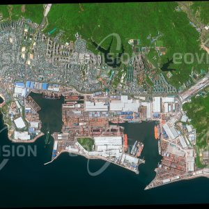 """Das Satellitenbild """"ULSAN - Südkorea"""" ist dem Bildband """"NEW HUMAN FOOTPRINT - Unsere Welt im Umbruch"""" entnommen. Bildbeschreibung: Ulsan im Südosten der Halbinsel Korea beherbergt die weltweit größte Werft. Für die Entwicklung dieser von Hyundai Heavy Industries betriebenen Werft war der gute Zugang des Standorts zum Meer wesentlich. Die Aufnahme verdeutlicht die Ausdehnung des Werftgeländes, unter anderem sind Trockendocks und Schiffe in unterschiedlichen Stadien der Fertigstellung zu sehen. An das Gelände schließen sich Wohnsiedlungen für die zahlreichen Arbeiter der Werft an."""