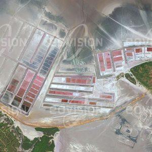 """Das Satellitenbild """"BELO SUR MER - Madagaskar"""" ist dem Bildband """"NEW HUMAN FOOTPRINT - Unsere Welt im Umbruch"""" entnommen. Bildbeschreibung: Unweit von Belo sur Mer erstrecken sich am flachen Rand der Lagune Salinen, in denen durch Verdunsten von Wasser schrittweise Salz angereichert wird. Diese Art der Salzgewinnung ist in Küstenbereichen in warmen Klimazonen weit verbreitet. Probleme treten dort auf, wo die Wasserqualität unter Verschmutzung leidet."""