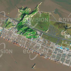 """Das Satellitenbild """"YANGSHAN PORT - China"""" ist dem Bildband """"NEW HUMAN FOOTPRINT - Unsere Welt im Umbruch"""" entnommen. Bildbeschreibung: Da der am Ufer des Jangtse gelegene Hafen Shanghais wegen seiner Gezeitenabhängigkeit die steigenden Gütermengen nicht mehr bewältigte, wurde 25 Kilometer vor der Küste ein neuer Tiefseehafen errichtet. Auf künstlich erweiterten Inseln entstand in der Hangzhou-Bucht ein Containerhafen mit dem weltweit größten automatisierten Terminal, an dem 2015 mehr als 36 Millionen Standardcontainer umgeschlagen wurden. Der Vollausbau des Hafens ist für 2020 geplant. Der Hafen ist über die Donghai-Brücke erreichbar, mit 32,5 Kilometern Länge die längste Meeresbrücke der Welt."""