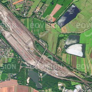 """Das Satellitenbild """"MASCHEN - Deutschland"""" ist dem Bildband """"NEW HUMAN FOOTPRINT - Unsere Welt im Umbruch"""" entnommen. Bildbeschreibung: Der bis Mitte der 1970er Jahre erbaute Rangierbahnhof Maschen im Süden von Hamburg ist der größte Europas und der zweitgrößte weltweit. Auf einer Länge von etwa 7 Kilometern und einer Breite von 700 Metern wurden Gleise mit einer Gesamtlänge von 300 Kilometern verlegt. Ursprünglich für 11.000 Güterwagen pro Tag ausgelegt, ist der Bahnhof eine wichtige Komponente im Güterverkehr, der den Hamburger Hafen bedient."""