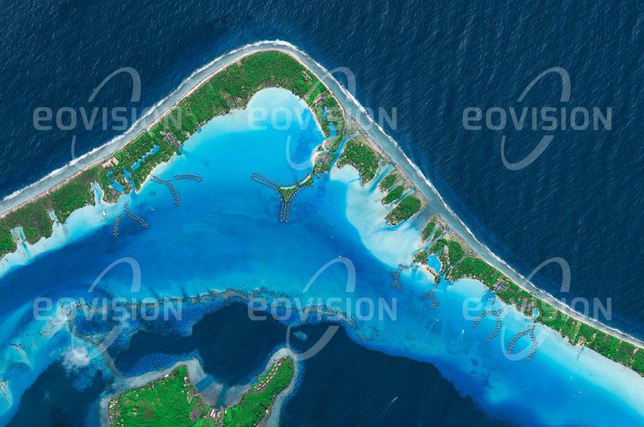 """Das Satellitenbild """"BORA BORA - Franz. Polynesien"""" ist dem Bildband """"NEW HUMAN FOOTPRINT - Unsere Welt im Umbruch"""" entnommen. Bildbeschreibung: Mit türkisfarbenem Wasser an weißen Sandstränden entspricht Bora Bora dem touristischen Inseltraum. Mit Tahiti gehört die Insel zu den französischen Gesellschaftsinseln. Um sie herum erstreckt sich ein Barriereriff, auf dessen flachen Inseln Hotel- und Bungalowanlagen errichtet wurden. Besonders begehrt waren in jüngster Vergangenheit die als Pfahlbauten direkt im seichten Wasser der Lagune errichteten Hüttendörfer, in denen Naturnähe mit luxuriösem Urlaubserleben verbunden wird."""