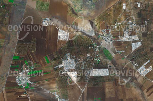 """Das Satellitenbild """"SHAMARIN - Syrien - Türkei"""" ist dem Bildband """"NEW HUMAN FOOTPRINT - Unsere Welt im Umbruch"""" entnommen. Bildbeschreibung: Seit Beginn des Bürgerkriegs in Syrien im Jahr 2011 sind etwa 3,5 Millionen Menschen als Folge der Auseinandersetzungen in die Türkei geflüchtet. Die Satellitenaufnahme zeigt ein Dorf nahe der nordsyrischen Grenze bei Az'az, dessen ursprünglichen Siedlungs- und Landwirtschaftsstrukturen weitgehend von den Containerdörfern und Zeltlagern der Flüchtlinge überlagert sind. Das Flüchtlingskommissariat der Vereinten Nationen UNHCR schätzt, dass 5,6 Millionen Menschen ins Ausland und 6,1 Millionen innerhalb Syriens vertrieben wurden."""
