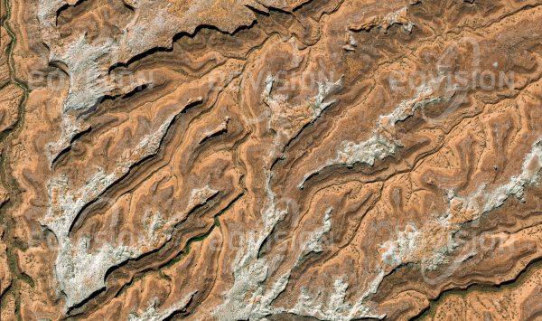 """Das Satellitenbild """"FOLD CANYON - USA"""" ist dem Bildband """"UNTOUCHED NATURE - Naturlandschaften in Satellitenbildern"""" entnommen. Bildbeschreibung: Reste der harten Deckschicht haben im Grand Staircase Escalante National Monument der Erosion widerstanden, dazwischen graben sich die Flüsse immer tiefer in die Sedimentschichten ein."""