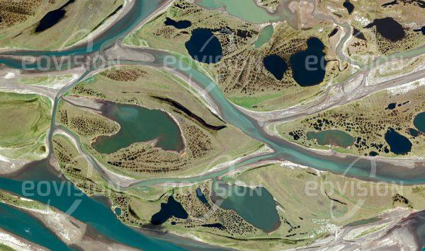 """Das Satellitenbild """"COLVILLE RIVER - USA"""" ist dem Bildband """"UNTOUCHED NATURE - Naturlandschaften in Satellitenbildern"""" entnommen. Bildbeschreibung: Nicht weit von den Ölförderanlagen der Prudhoe Bay entfernt bilden sich im flachen Flussbett des Colville Rivers Inseln, die ihrerseits durch ein dichtes Muster kleiner Seen bedeckt sind. Die feinen, netzartigen Strukturen sind eine Folge des wiederholten Gefrierens und Auftauens des wasserreichen Bodens. Im Winter wird der gefrorene Fluss auch als Eisstraße für die Versorgung der nördlich liegenden Siedlungen genützt. Karibus, Wölfe und Grizzlybären, aber auch die weltweit höchste Dichte brütender Raubvögel sind hier zu finden."""