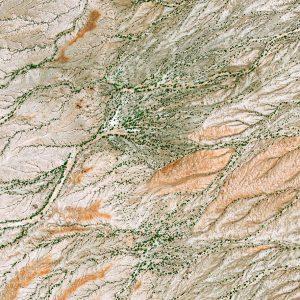 """Das Satellitenbild """"TURKANA - Kenia"""" ist dem Bildband """"UNTOUCHED NATURE - Naturlandschaften in Satellitenbildern"""" entnommen. Bildbeschreibung: Westlich des Turkanasees in Kenia bildet leicht erodierendes Sedimentgestein die Grundlage für eine karge Savanne. Bäume und Sträucher wachsen hier fast ausschließlich unmittelbar neben den Flussläufen, wo in tieferen Bodenschichten auch während der Trockenzeit Wasser zu finden ist. Vereinzelte Hütten und Einfriedungen deuten auf eine dünne Besiedelung durch Menschen hin, die von Ziegenhaltung leben."""