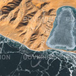 """Das Satellitenbild """"ZIGUI CUO - China"""" ist dem Bildband """"UNTOUCHED NATURE - Naturlandschaften in Satellitenbildern"""" entnommen. Bildbeschreibung: Durch den Himalaya von den Monsunregen abgeschirmt ist das Hochland von Tibet trocken und wüstenhaft. Die Trockenheit wird in der schneefreien Landschaft um den eisbedeckten See deutlich."""