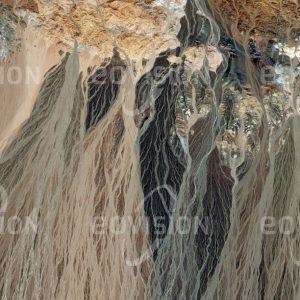 """Das Satellitenbild """"BAYTIK SHAN - China"""" ist dem Bildband """"UNTOUCHED NATURE - Naturlandschaften in Satellitenbildern"""" entnommen. Bildbeschreibung: Nahe der Grenze Chinas zur Mongolei haben sich im Übergang des Baytik Shan in die Dsungarei ausgedehnte Schwemmfächer mit einem feinen Netzwerk von Abflussrinnen ausgebildet. In den zahlreichen Trockentälern versickert das wenige Regenwasser rasch, nachdem es unterschiedlich gefärbtes Material aus verschiedenen Gesteinsschich-ten mitgenommen und abgelagert hat."""