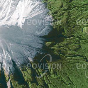 """Das Satellitenbild """"MOUNT TARANAKI - Neuseeland"""" ist dem Bildband """"UNTOUCHED NATURE - Naturlandschaften in Satellitenbildern"""" entnommen. Bildbeschreibung: Der im Südwinter schneebedeckte, 2.518 Meter hohe Mount Taranaki auf der Nordinsel Neuseelands ist ein geologisch sehr junger Vulkan mit einer ausgeprägten Kegelform. Bereits im Jahr 1881 wurde um den Berg ein annähernd kreisförmiges Waldschutzgebiet errichtet, das seit 1900 den Hauptteil des Egmont-Nationalparks bildet. An der Grenze des Nationalparks geht der Regenwald abrupt in eine intensiv kultivierte Landschaft über."""