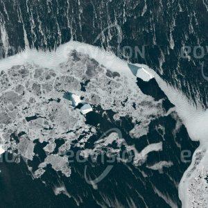 """Das Satellitenbild """"ANTARCTIC SOUND - Antarktis"""" ist dem Bildband """"UNTOUCHED NATURE - Naturlandschaften in Satellitenbildern"""" entnommen. Bildbeschreibung: Unterschiedlich dicke und alte Eisschollen treiben mit vereinzelten kleineren Eisbergen vor der Antarktis inmitten von Eisgries, welches vom heftigen Wind zusammengeschoben wird. In den letzten Jahrzehnten hat die Erderwärmung zu vermehrtem Abbrechen von Eisbergen von den Schelfeisflächen um die Antarktis geführt. Mit Dicken bis zu mehreren 100 Metern und Flächen, die 10.000 Quadratkilometer überschreiten können, stellen Eisberge eine große Gefahr für die Schifffahrt dar."""