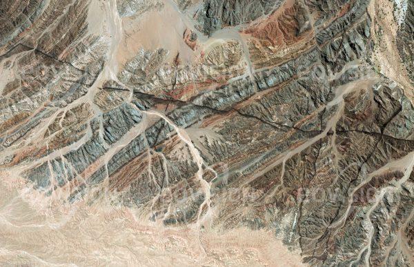 """Das Satellitenbild """"GOANIKONTES - Namibia"""" ist dem Bildband """"WÜSTEN - Lebensraum der Extreme"""" entnommen. Bildbeschreibung: Südlich des nur zeitweise Wasser führenden Swakop-Flusses erstreckt sich ein Felsgebiet, das im Satellitenbild ausgeprägte geologische Bruchlinien zeigt. Gut sichtbar ist die Faltung der Gesteinsschichten, die unter anderem aus granitischen Gneisen und Quarzit-Sedimenten bestehen. Die Landschaft trägt wegen ihrer lebensfeindlichen Bedingungen auch die Bezeichnung """"Mondlandschaft"""". Bekannt ist die Region auch für Funde von Uran und Boltwoodit, Kristallen eines seltenen Minerals. Nur 25 Kilometer weiter westlich liegt Swakopmund an der Mündung des Swakops in den Pazifik."""