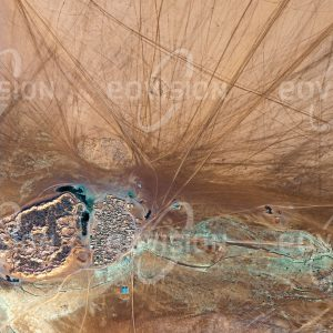 """Das Satellitenbild """"TEGGUIDA-N-TESSOUM - Niger"""" ist dem Bildband """"WÜSTEN - Lebensraum der Extreme"""" entnommen. Bildbeschreibung: Ein dichtes Netz von Fahrtrouten führt quer durch die Wüste zur Oasenstadt Tegguida. Die Wirtschaft der Oase beruht auf der Herstellung von Salz, das in zahlreichen kreisförmigen Verdunstungsbecken aus salzhaltigem Grundwasser gewonnen wird. Wegen der guten Befahrbarkeit der Ton-ebene von Talak sind die Reisenden nicht auf Straßen fixiert, sondern können beliebige Richtungen wählen."""
