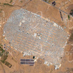 """Das Satellitenbild """"AZ-ZAATARI - Jordanien"""" ist dem Bildband """"WÜSTEN - Lebensraum der Extreme"""" entnommen. Bildbeschreibung: Kriegerische Konflikte sind der häufigste Grund, dass Menschen ihre Heimat verlassen. Wie die Konflikte selbst sind daher auch Flüchtlingslager kein neues Phänomen. Das für maximal 80.000 Bewohner geplante Az-Zaatari im Norden Jordaniens gehört zu den größten Flüchtlingslagern der Welt. Es entstand 2012 als Folge des syrischen Bürgerkriegs, durch den bis 2015 fast 12 Millionen Menschen vertrieben wurden. Im März 2013 beherbergte das Lager sogar mehr als 156.000 Menschen. Unter der Leitung des UNHCR (Flüchtlingswerk der Vereinten Nationen) hat sich Az-Zataari zu einer eigenen Stadt entwickelt."""