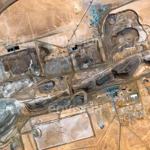 """Das Satellitenbild """"TASIAST-MINE - Mauretanien"""" ist dem Bildband """"WÜSTEN - Lebensraum der Extreme"""" entnommen. Bildbeschreibung: Im Tagebau der Tasiast-Mine im Westen Mauretaniens wird seit 2008 Gold gefördert. Aufgrund hoher Anlaufkosten war der Start schwierig, insgesamt werden hier jedoch etwa 7,5 Millionen Unzen (230 Tonnen) förderbares Gold erwartet. Für jedes Gramm Gold muss fast eine Tonne Gestein verarbeitet werden."""