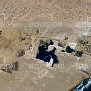 """Das Satellitenbild """"ELIZABETH BAY - Namibia"""" ist dem Bildband """"WÜSTEN - Lebensraum der Extreme"""" entnommen. Bildbeschreibung: Um 1908 wurden in der Region um Elizabeth Bay Diamanten gefunden, die vom Oranje-Fluss in den Atlantik geschwemmt und von diesem an der Küste abgelagert worden waren. Ab 1991 wurden die Diamanten in großem Maßstab gefördert. Heute werden Diamanten vor der Küste abgebaut. Das Städtchen Elizabeth Bay ist weitgehend eine verfallende Geisterstadt."""