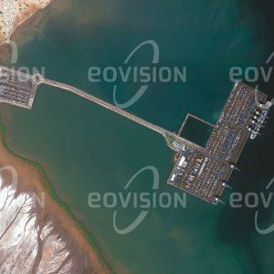 """Das Satellitenbild """"DJIBOUTI - Dschibuti"""" ist dem Bildband """"WÜSTEN - Lebensraum der Extreme"""" entnommen. Bildbeschreibung: In der Hauptstadt Djiboutis leben mehr als 60% der Einwohner des Landes, das zu den am wenigsten entwickelten der Erde zählt. Die strategische Lage am Eingang zum Roten Meer stellt eine Grundlage für seine Rolle als Handelsknotenpunkt dar. Wichtig ist dabei das Doraleh Container Terminal, eines der modernsten Afrikas, das im Jahr 2014 verstaatlicht wurde."""