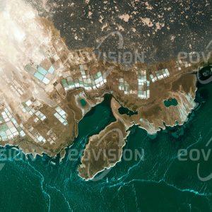 """Das Satellitenbild """"AFRERASEE - Äthiopien"""" ist dem Bildband """"WÜSTEN - Lebensraum der Extreme"""" entnommen. Bildbeschreibung: Das hypersaline Wasser des in der Danakil-Senke gelegenen Afrerasees wird seit Jahrhunderten für die Salzgewinnung genutzt. In traditioneller Weise wird das Salz hier in Form von Salzblöcken gewonnen und von Kamelkarawanen abtransportiert. Insgesamt werden die Salzvorkommen am See auf 290 Millionen Tonnen geschätzt. Durch den Ausbruch des etwa 80 Kilometer östlich gelegenen Nabro im Jahr 2011 gelangten allerdings größere Mengen Schwefelsäure in den See, sodass das Salz seither nicht genießbar ist."""