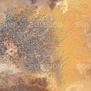 """Das Satellitenbild """"TAOUDENNI - Mali"""" ist dem Bildband """"WÜSTEN - Lebensraum der Extreme"""" entnommen. Bildbeschreibung: Etwa ab dem Ende des 16. Jahrhunderts wurde nahe der Stadt Taoudenni Salz gewonnen. Heute hat sich die Salzgewinnung etwa 10 Kilometer weiter in den Südwesten verschoben. Hier liegt einige Meter unter der Oberfläche eine hochwertige Salzschicht. Mit einfachsten Mitteln werden hunderte bis zu vier Meter tiefe Löcher in den Sand und Lehm gegraben. Aus der darunter liegenden Salzschicht werden Platten geschlagen, die zu 30 Kilogramm schweren Salzbarren bearbeitet werden. Karawanen transportieren diese nach Timbuktu."""