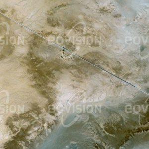 """Das Satellitenbild """"ZOUERAT - Mauretanien"""" ist dem Bildband """"WÜSTEN - Lebensraum der Extreme"""" entnommen. Bildbeschreibung: Über die 800 Kilometer lange Bahnlinie, die das Eisenerzabbaugebiet Zouerat mit dem Hafen Nouadhibou am Atlantik verbindet, bringen zweieinhalb Kilometer lange Züge mit bis zu 210 Waggons jeweils 17.000 Tonnen Eisenerz zum Hafen. Von drei bis vier Diesellokomotiven gezogen fährt der längste Zug der Welt mit 30 bis 40 Stundenkilometern durch die Wüste."""